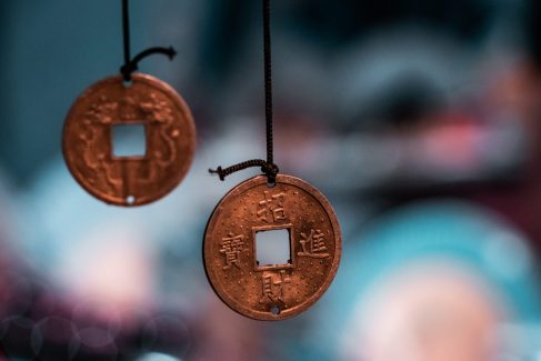 Oriental, magical pendants. Traditional asiatic and chinese currency, transformed into fortune coins with powerful engravings. Bronze, copper, gold necklace, black thread, blurry background.